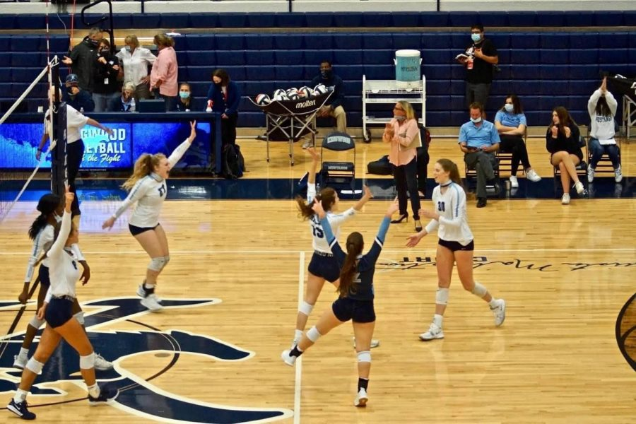 The Varsity team celebrates an ace by senior Megan Wilson. Photo courtesy of Diane Kahler.